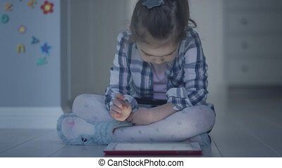 Girl with tablet sitting on floor