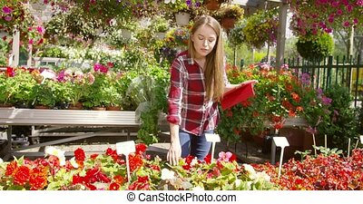 Girl with tablet working in blooming garden - Young casual...