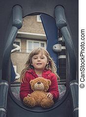 Girl with teddy bear on a slide