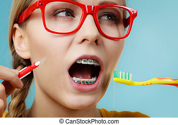 Girl with teeth braces using interdental and traditional...
