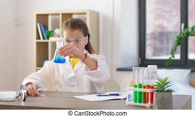 girl with test tubes studying chemistry at home