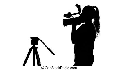 Girl with the camera in hand is in the studio. White. Silhouette