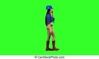Girl with the hammer on the belt goes sideways on a green background