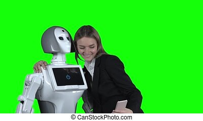 Girl with the robot is photographed and take a selfie . Green screen. Slow motion