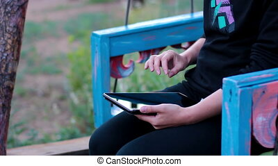 Girl with the tablet on a wooden swing hands