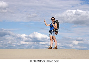 girl with thumb up hiking in desert