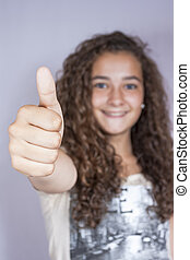 Girl with thumbs up, happy and successful. Studio Shot