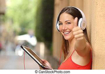 Girl with thumbs up using a tablet with headphones