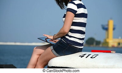 Girl With Touch Pad Sitting in Port. Slow Motion Effect