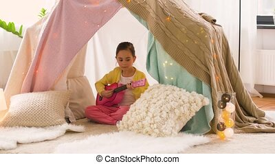 girl with toy guitar playing in kids tent at home