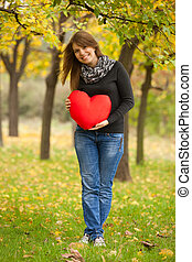 Girl with toy heart at autumn park.