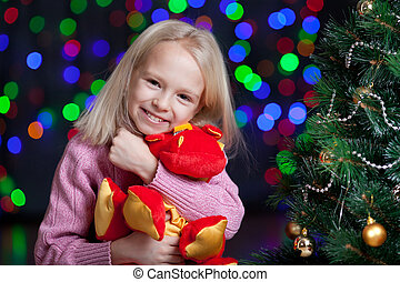 girl with toy in bright christmas background
