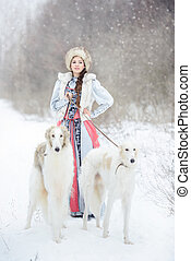 girl with two greyhounds walking in the winter