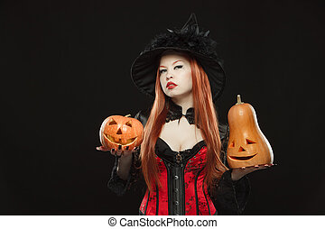 Girl with two Halloween pumpkin on black background