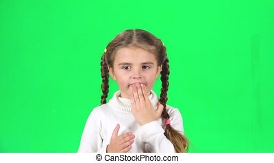 Girl with two pigtails is sending air kisses and smiling on...
