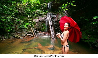 Girl with umbrella at waterfall