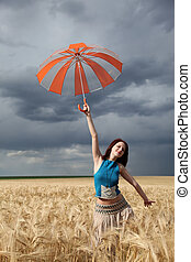 Girl with umbrella at wheat field at rainy day