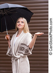 Girl with umbrella. Beautiful young blond hair woman holding umbrella and looking up
