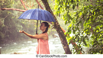 girl with umbrella in a rain forest