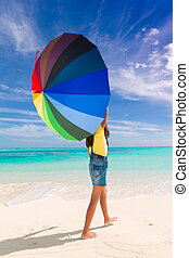 Girl with umbrella on beach