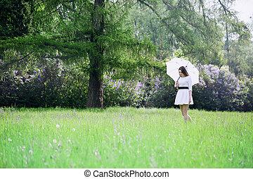 girl with umbrella walking through a meadow