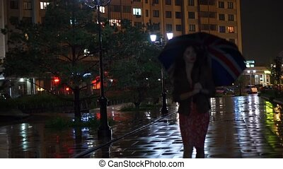 Girl with Union Jack umbrella walking at rainy night, slow...