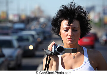 girl with videocamera on highway
