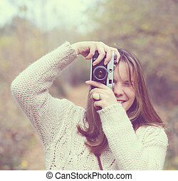 Girl with vintage camera taking photo outdoor