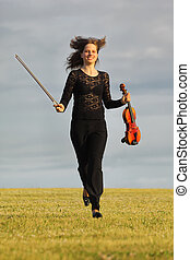girl with violin runs on grass against sky, front view