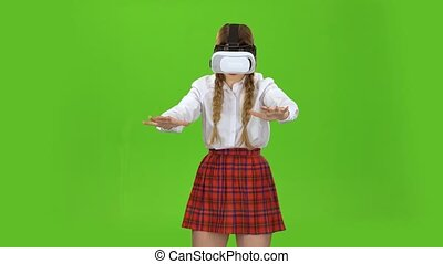 Girl with virtual reality glasses is playing. Green screen