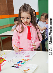 Girl With Watercolor And Paintbrush Painting At Desk