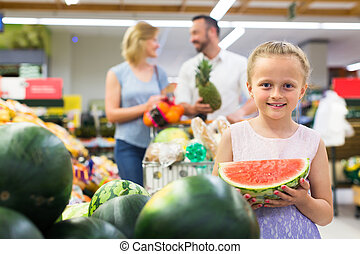 Girl with watermelon in fruit section