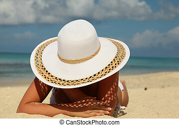 Girl with white hat on sand