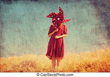 Girl with wind turbine at field