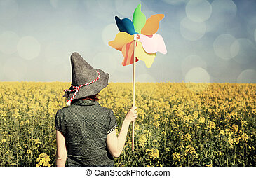 Girl with wind turbine at rapeseed field