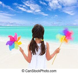 Girl with windmills on beach