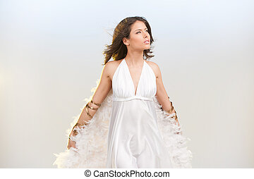 Girl with wings. Beautiful young woman with white wings looking away while standing isolated on colored background