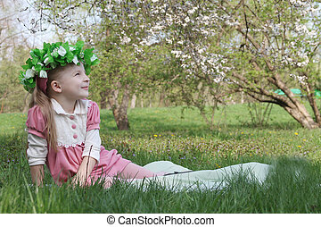 Girl with wreath under spring tree looking up