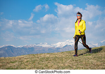 Girl with yellow down jacket strolls in the mountains