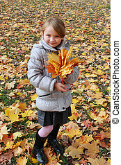 girl with yellow leaves in the park