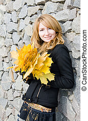 Girl with yellow leaves on a background a stone wall