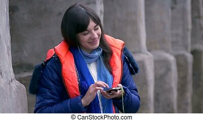 girl woman closed eyes listening to music on smartphone headphones in jacket and scarf