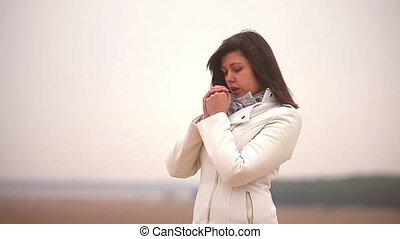 girl woman cold rubs his hands blowing autumn nature steppe...