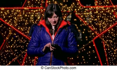 girl woman holding a smart phone looking at social media the night behind bokeh winter light