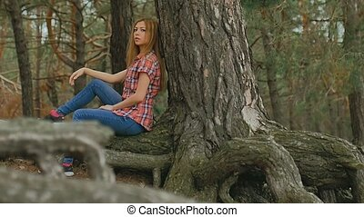 girl woman sits in large pine tree forest roots slow motion
