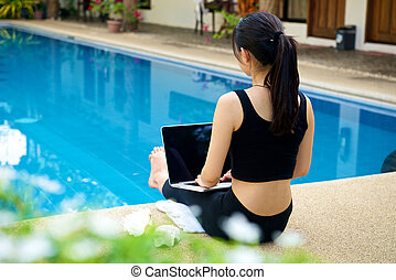 Girl work with laptop at pool