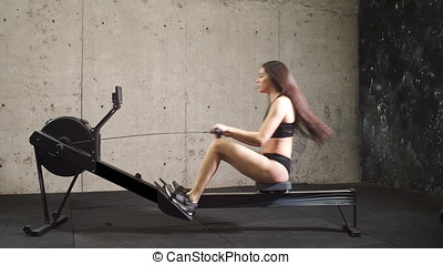 Girl Working Out On Rowing Machine. - Girl Working Out On...