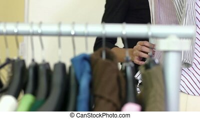 Young hispanic female dressmaker adjusting clothes on tailoring mannequin and smiling. Dolly shot