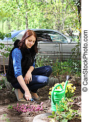 Girl works in a spring garden, plants flowers and soil grab with special rakes