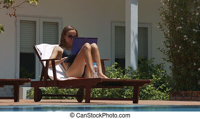 Girl Works on Notebook in Folding Chair by Pool